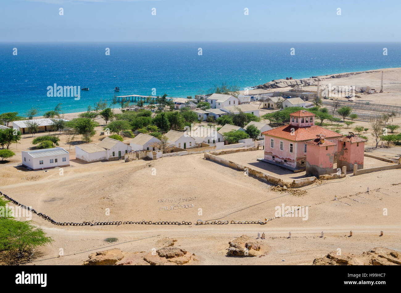 Small fishing village Mucuio with dominating Portuguese colonial building and white washed buildings in Angola. - Stock Image