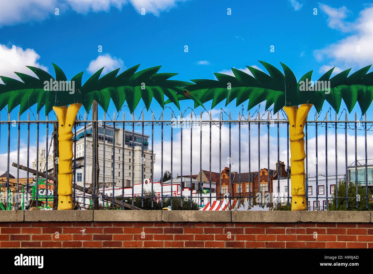 Palm trees and barbed wire fence of 'Adventure Island' Amusement Park & Funfair. Southend-on-sea, Essex,England - Stock Image