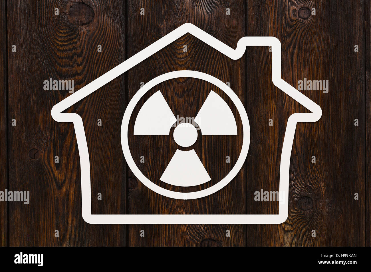 Paper house with radiation danger sign, abstract conceptual image - Stock Image