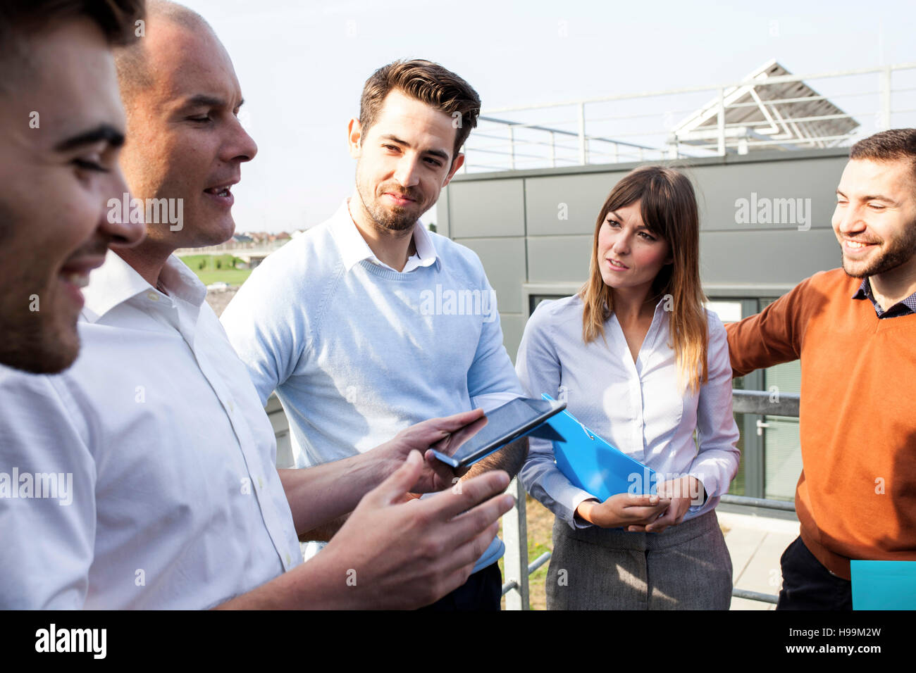 Group of business people talking outdoors - Stock Image