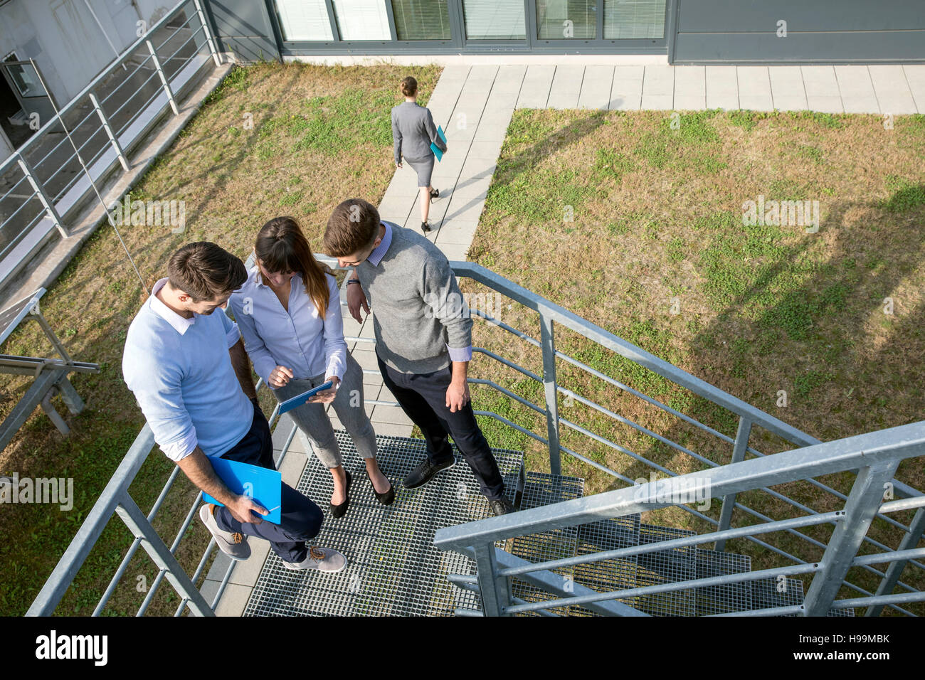Group of business people talking on stairway - Stock Image