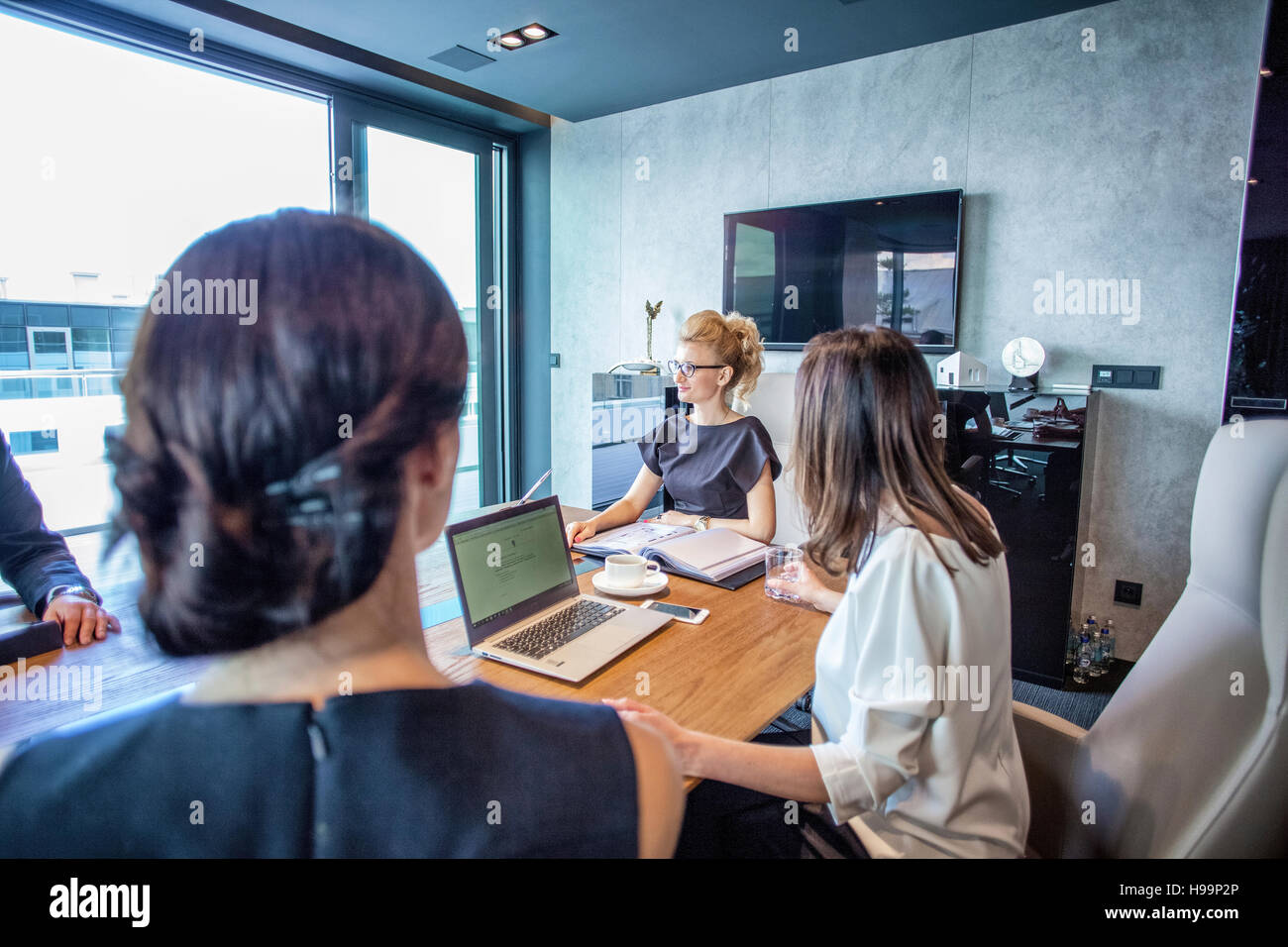 Businesswomen having a meeting in conference room - Stock Image