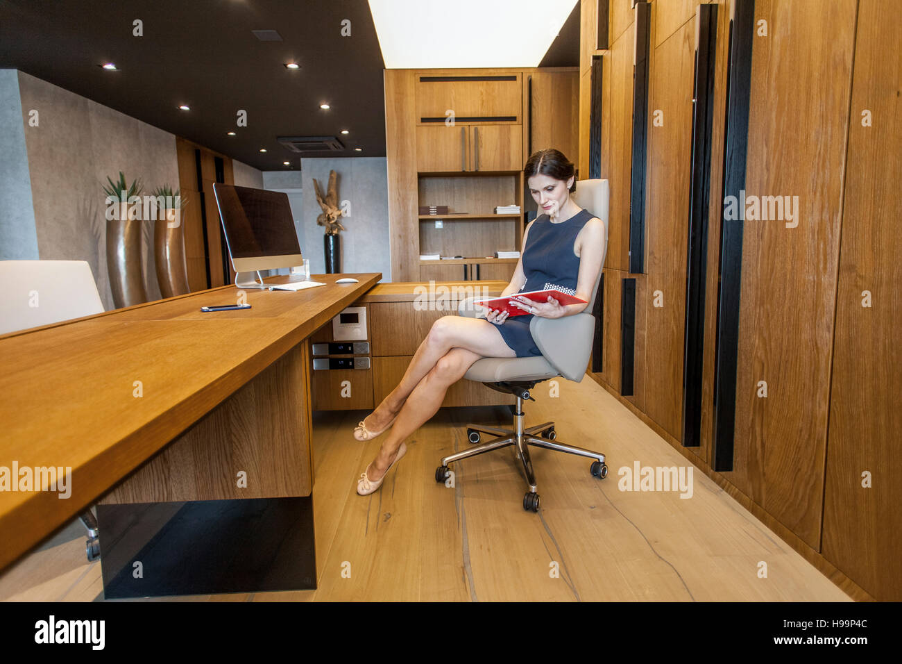 Businesswoman in mini dress sits at reception desk - Stock Image