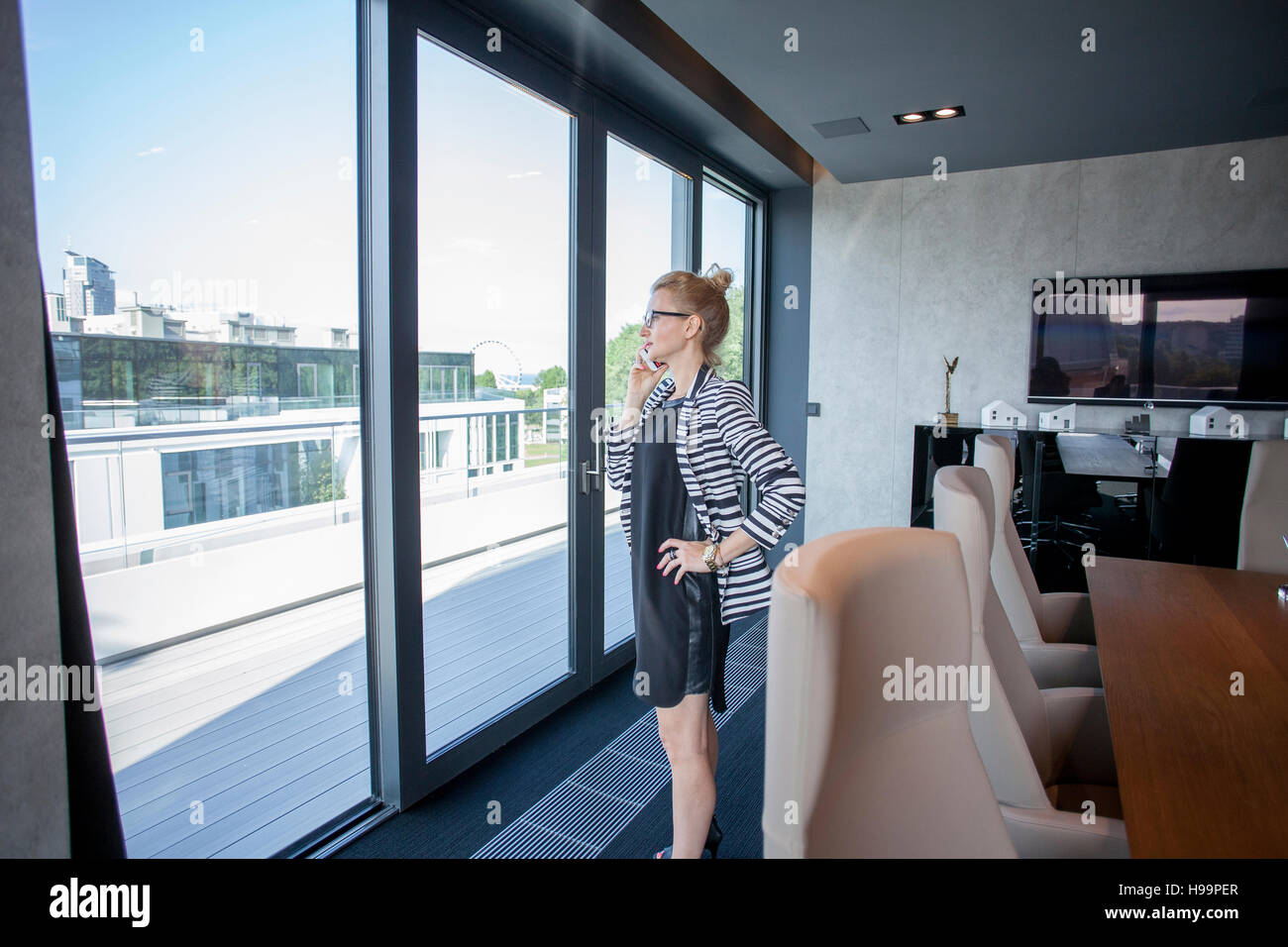 Businesswoman in office looking through window - Stock Image