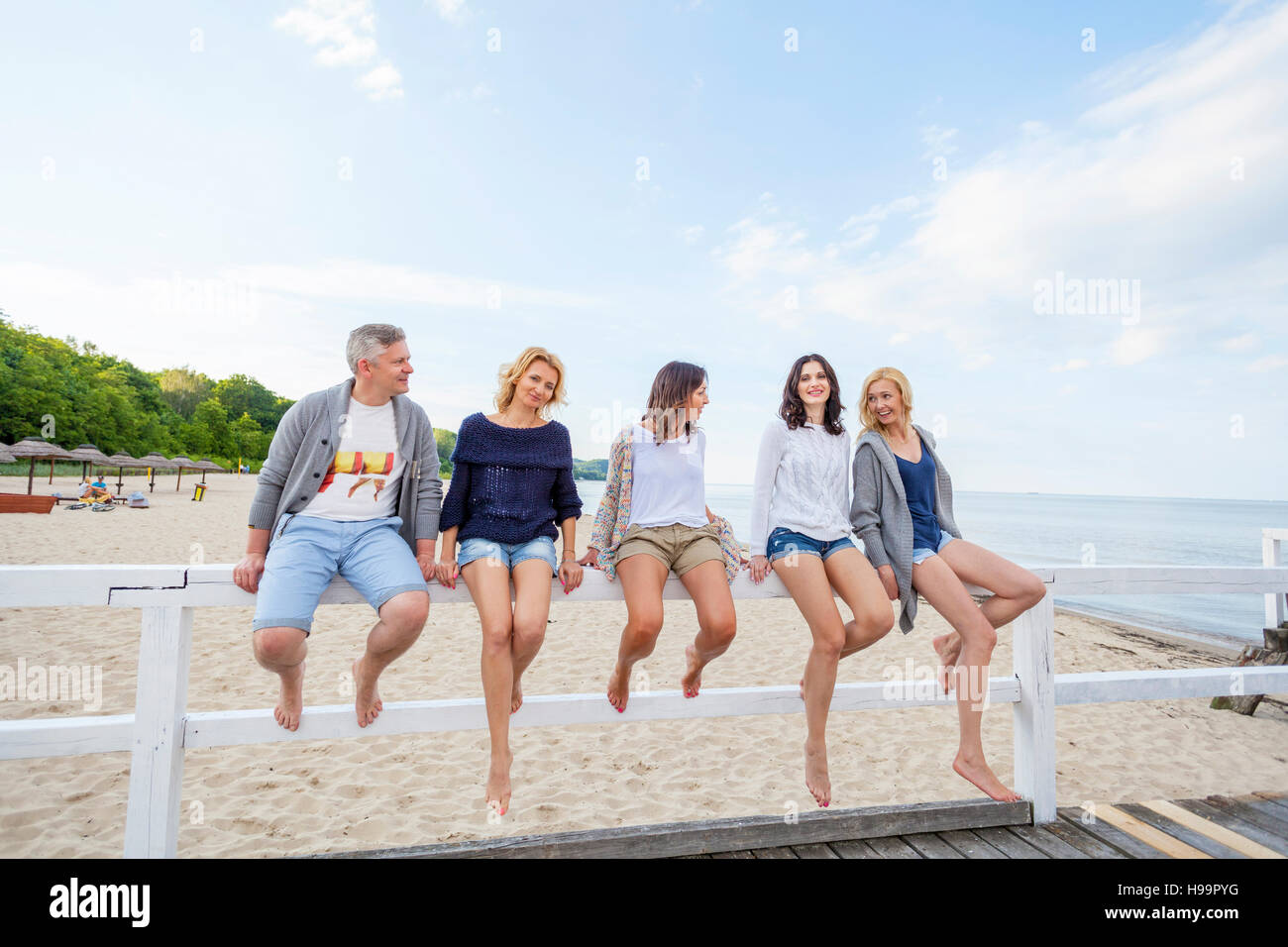 Group of friends take a break sitting on railing - Stock Image