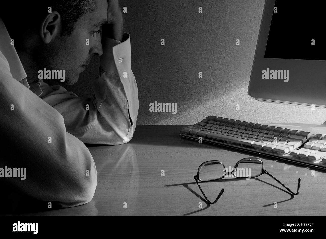 Thoughtful man at the computer. Black and white. - Stock Image