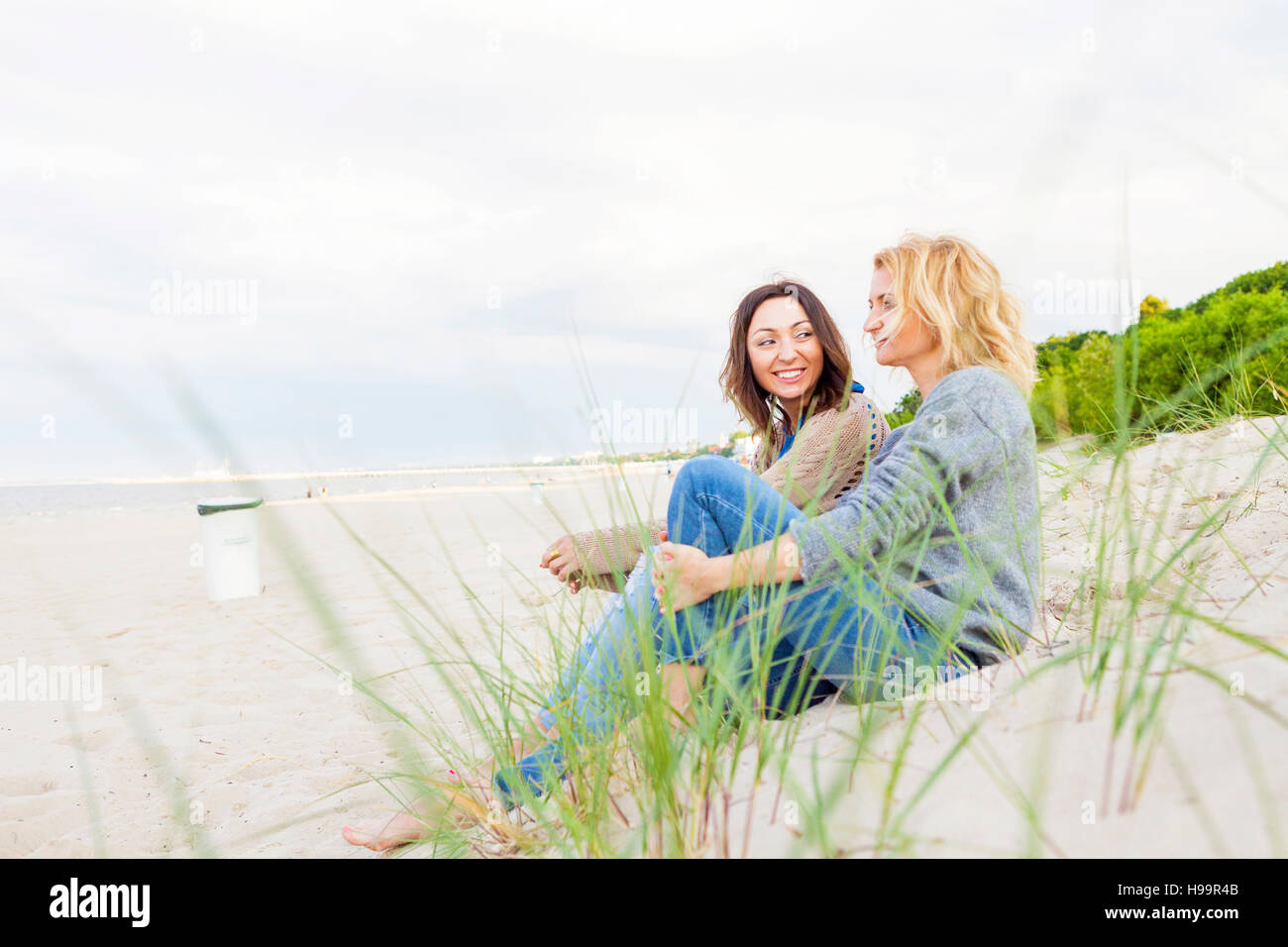 Two girlfriends relaxing on sandy beach - Stock Image