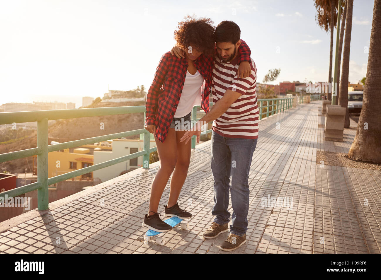 Boy showing girl with hand gestures how the skateboard works while holding her up and her arm around his shoulder - Stock Image