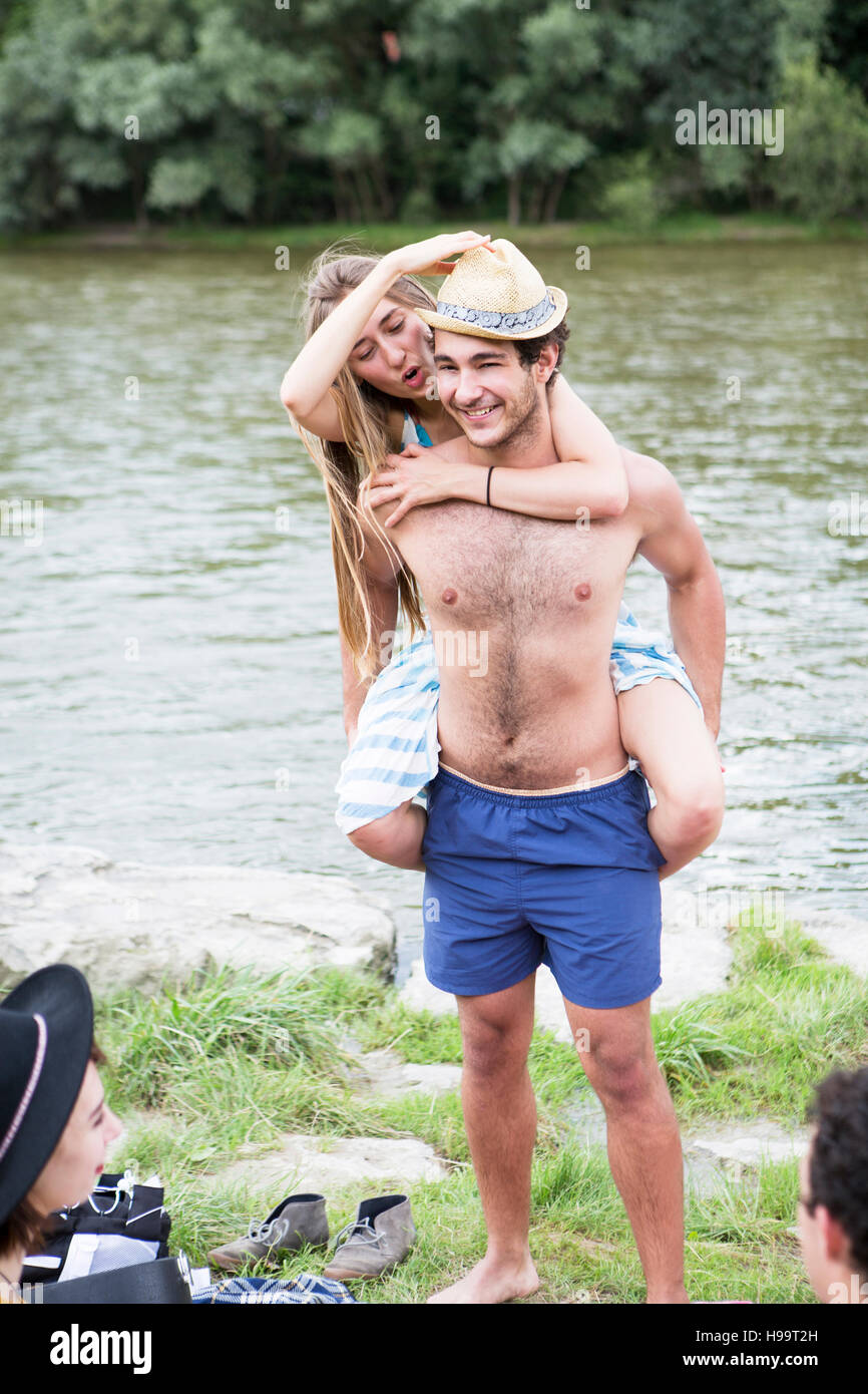 Young man giving girlfriend piggyback on the riverbank - Stock Image