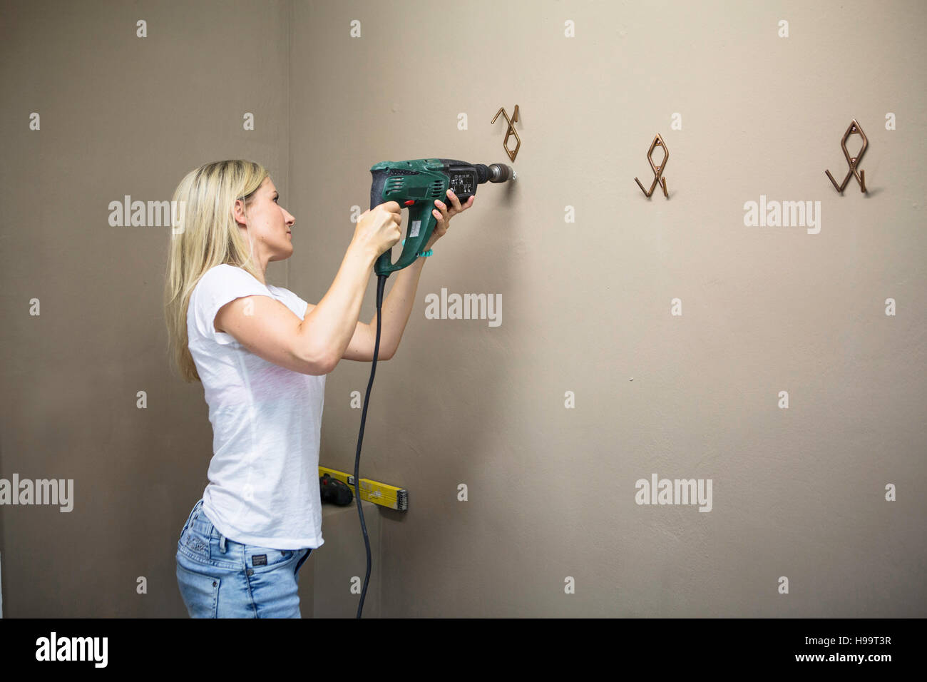 Woman using drill to fix coat hook in apartment - Stock Image