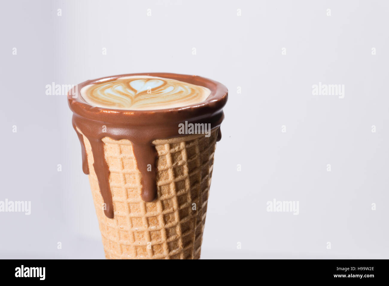 Coffee in waffle cone dipped in chocolate with drawings in cappuccino / latte milk foam, latte art, isolated Stock Photo