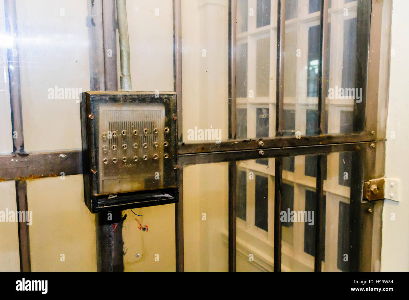 Intercom and steel barred doors in a prison, covered with toughened perspex for protection. - Stock Image