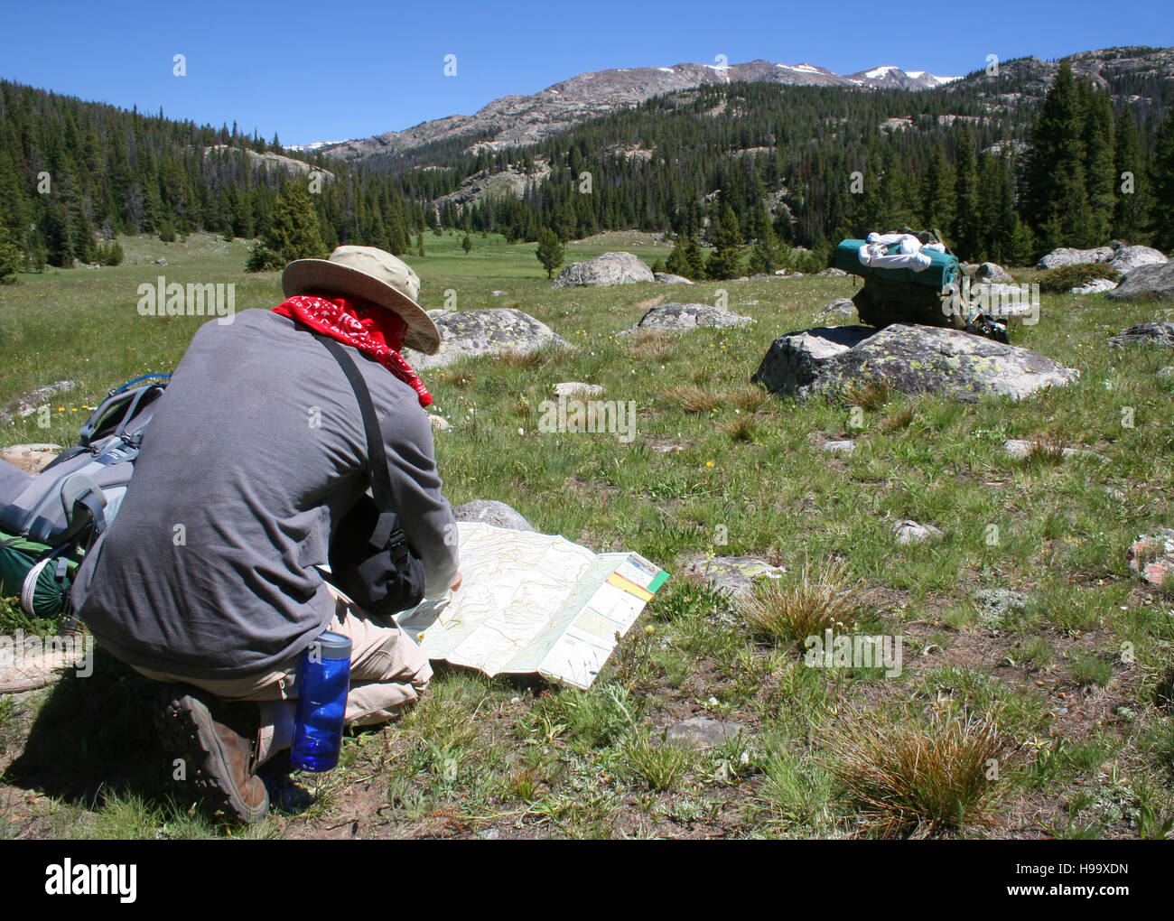 A hiker consults the map to navigate rugged mountain terrain. - Stock Image