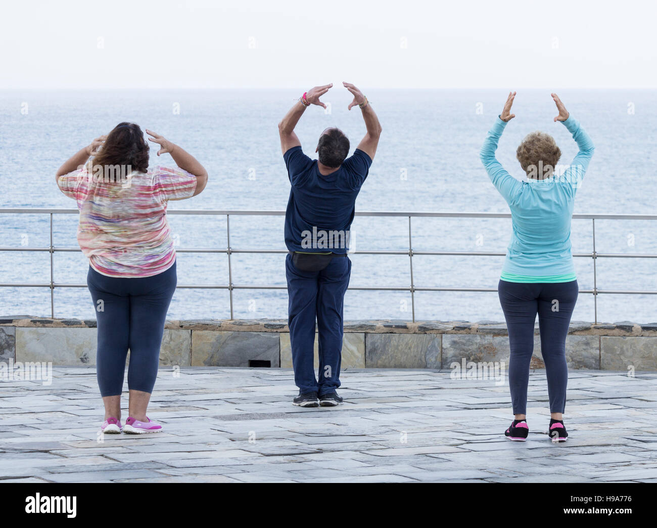Mature man and two mature women practicing Tai chi overlooking the sea Stock Photo