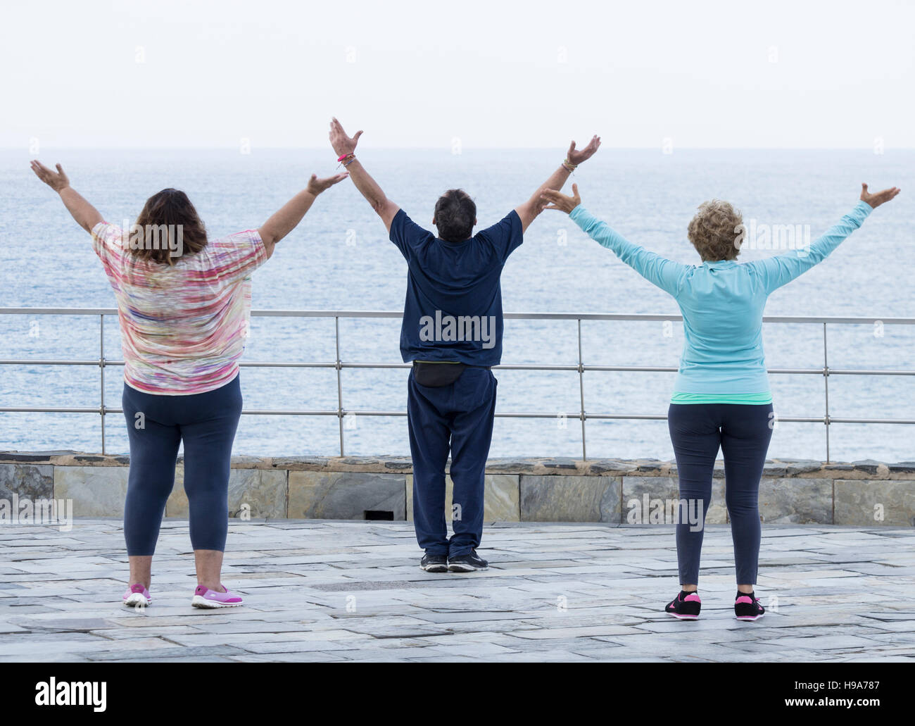 Mature man and two mature women practicing Tai chi overlooking the sea - Stock Image