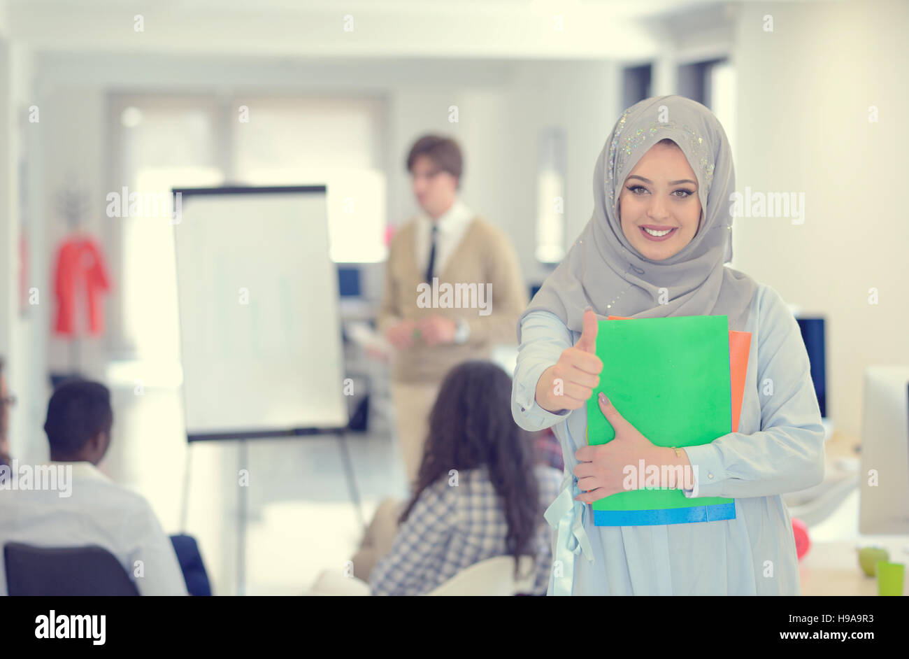 Arabic business woman working in team with her colleagues at startup office - Stock Image