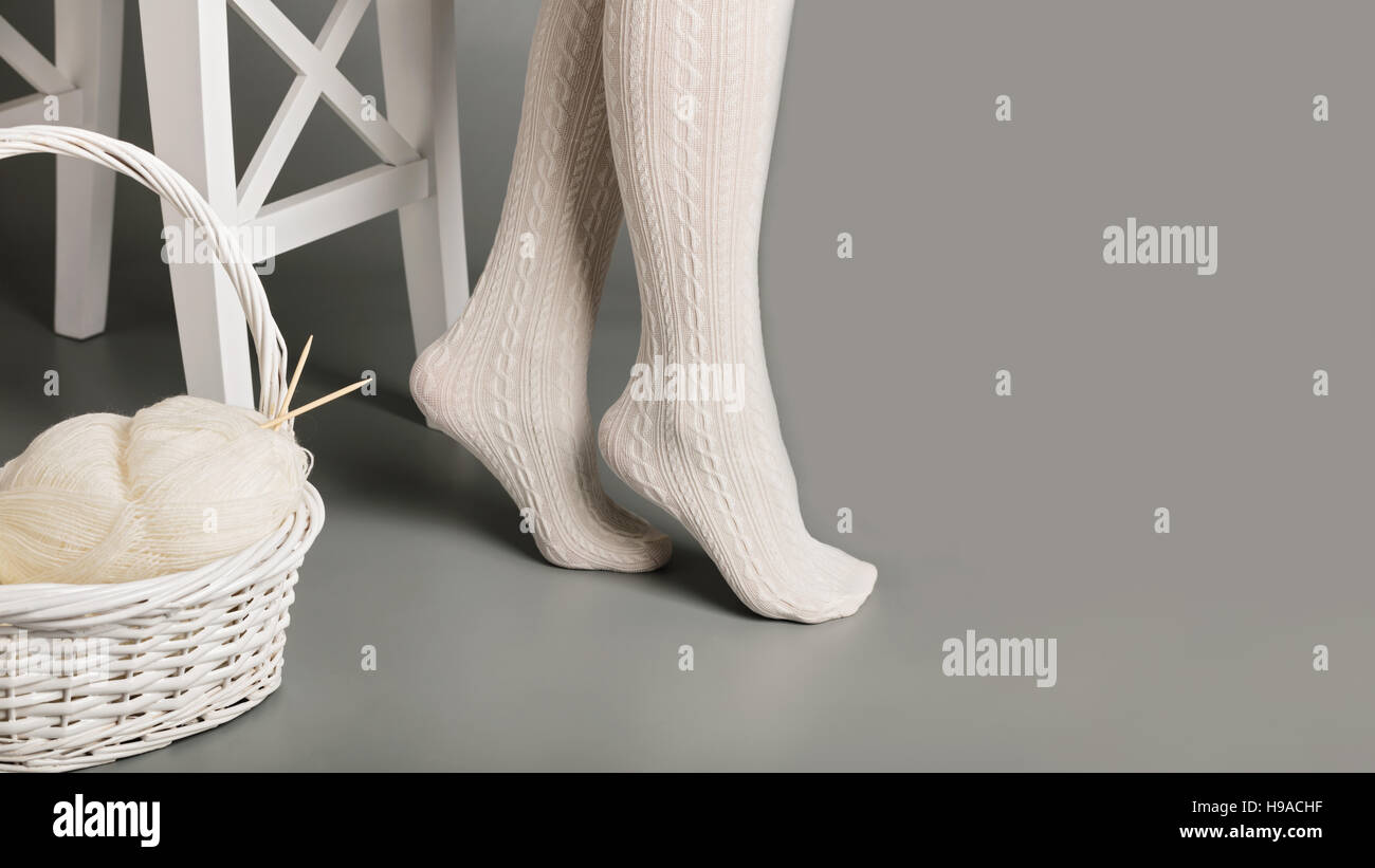 Female feet in white knitted tights near the basket with yarn and knitting. - Stock Image