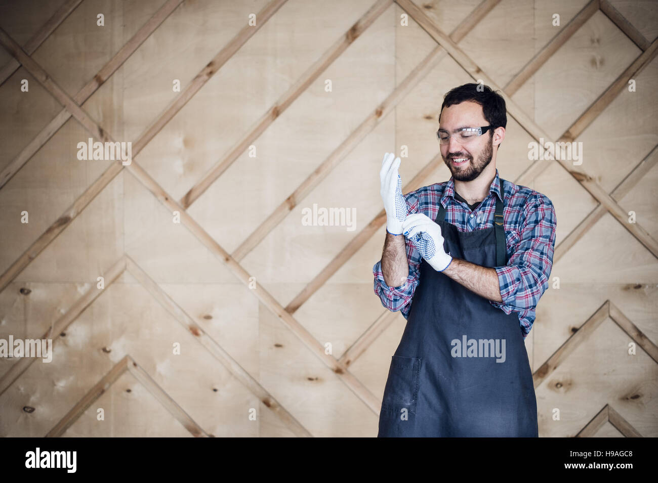 Portrait of a carpenter working in workshop wearing gloves - Stock Image