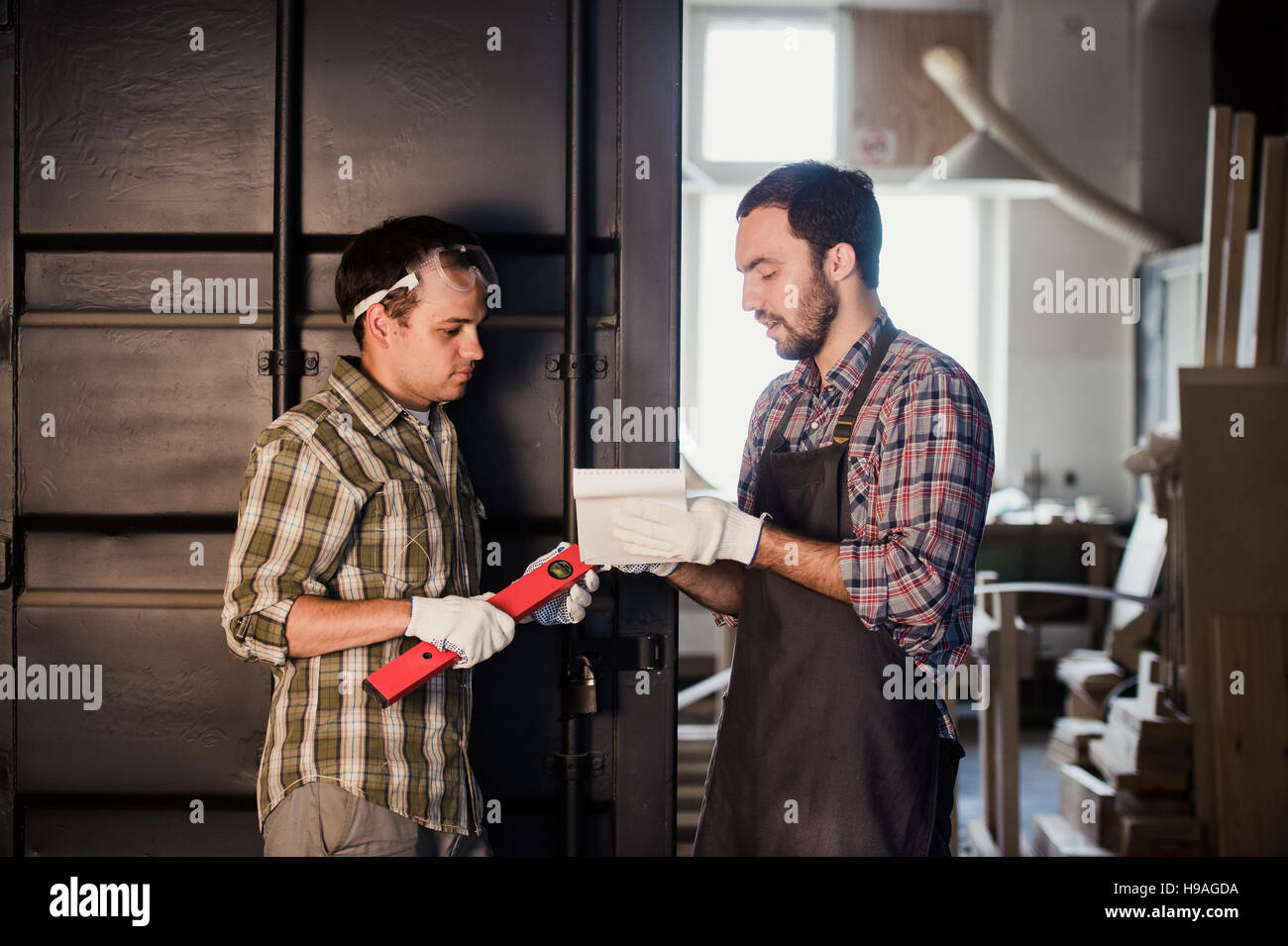 Two carpenters are talking while holding papers and ruler. One of them is wearing safety mask. Carpentry shop background - Stock Image