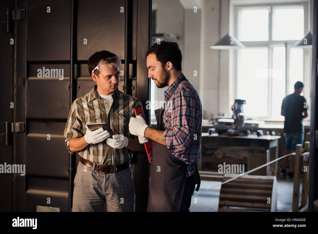 profession, technology and people concept - two workmen with tablet pc computer at workshop - Stock Image