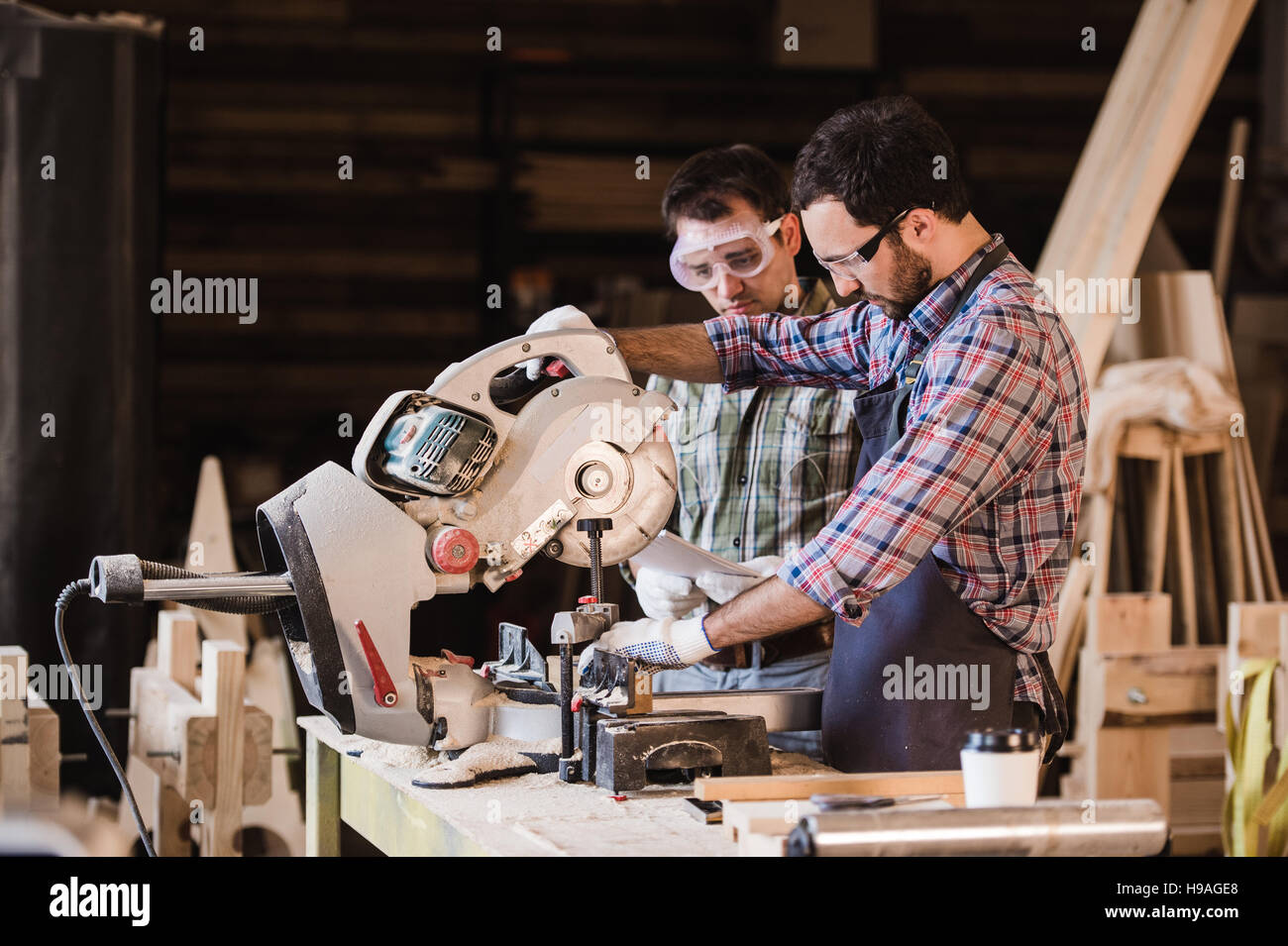 Inspector and carpenter discuss the process of making wood products for furniture - Stock Image