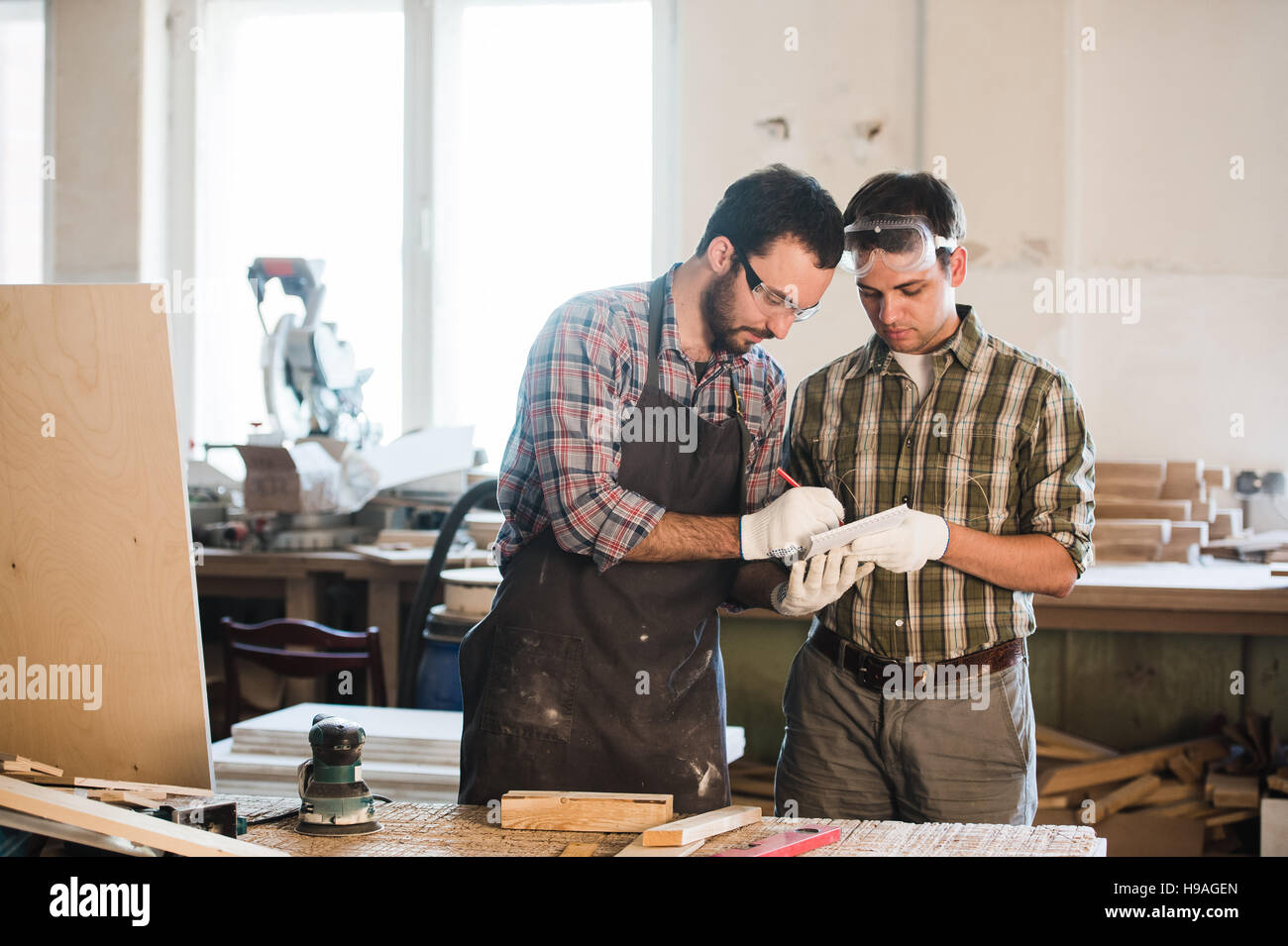 two man polishes boards. carpenter with a sander - Stock Image