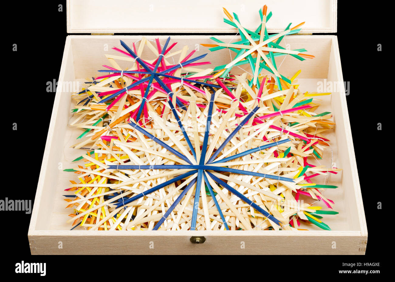 Straw stars Christmas decoration in wooden box. Handmade colorful decor for windows, as gifts or to hang on the Stock Photo