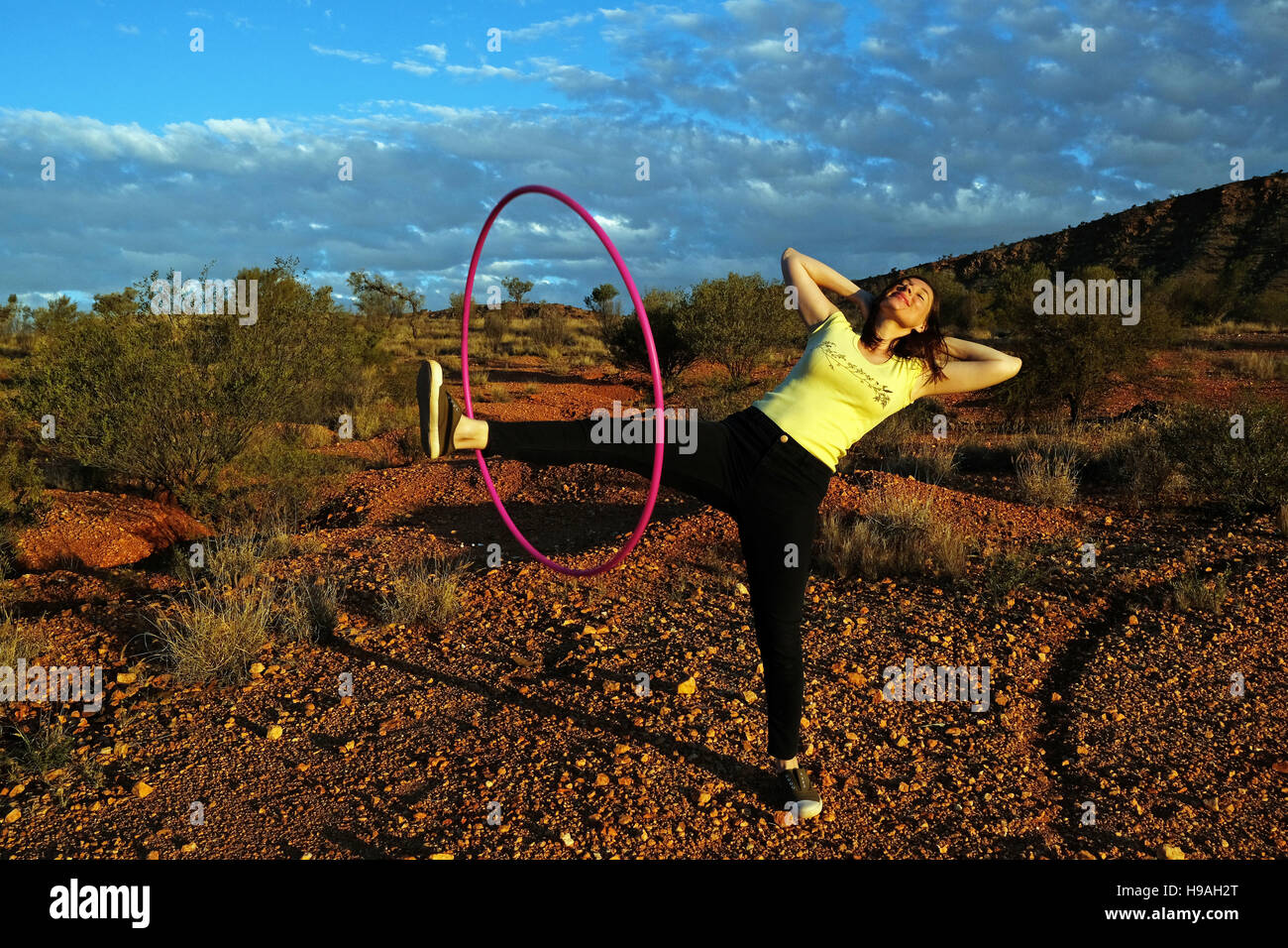 A woman exercises with a hula hoop in Alice Springs,  the MacDonnell Ranges, Northern Territory, Central Australia - Stock Image