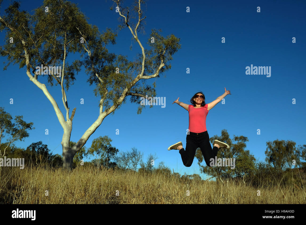 A woman leaps during an exercise in Alice Springs, the MacDonnell Ranges, Northern Territory, Central Australia - Stock Image
