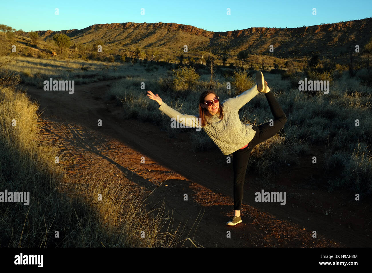 A woman stretches her legs and arms in front of the MacDonnell Ranges, Alice Springs, Northern territory, Central - Stock Image