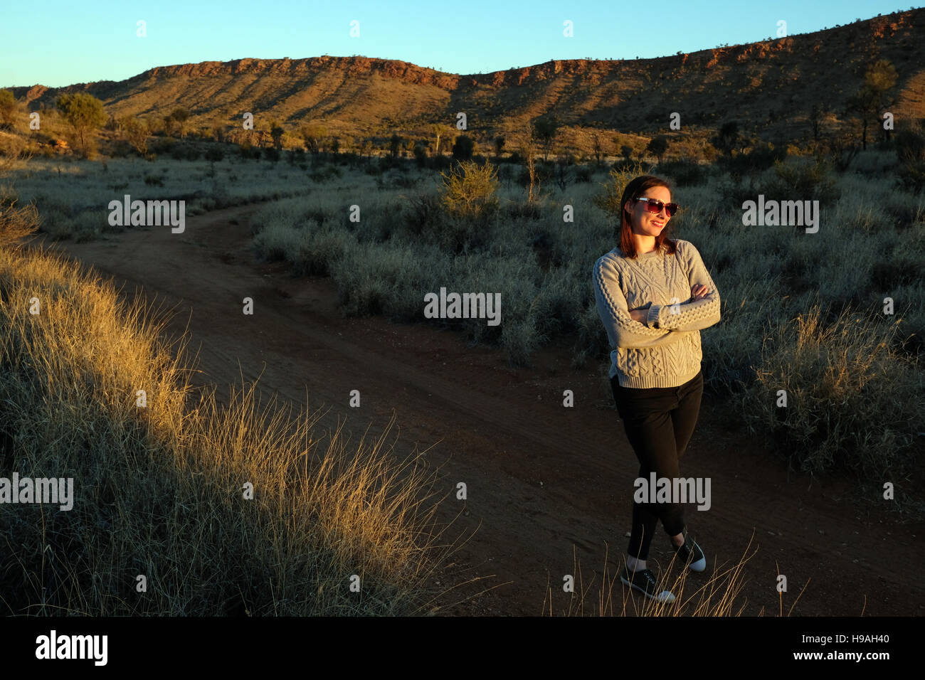 A woman watches the sunset in the MacDonnell Ranges, Alice Springs, Northern Territory, Central Australia - Stock Image