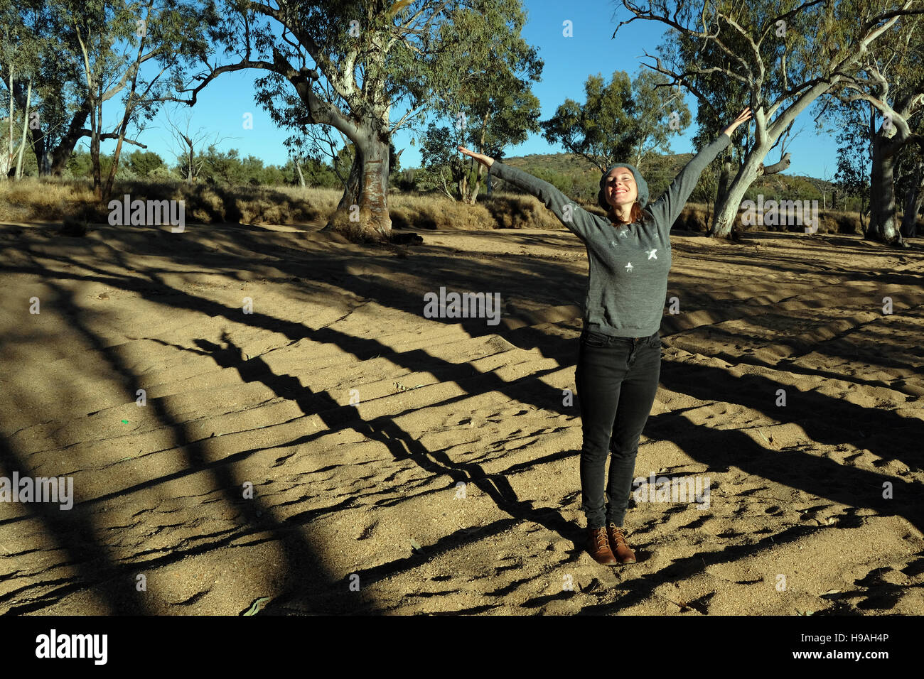 A young woman enjoys the morning sunshine at Roe Creek, Honeymoon Gap in the MacDonnell Ranges, Northern Territory, - Stock Image