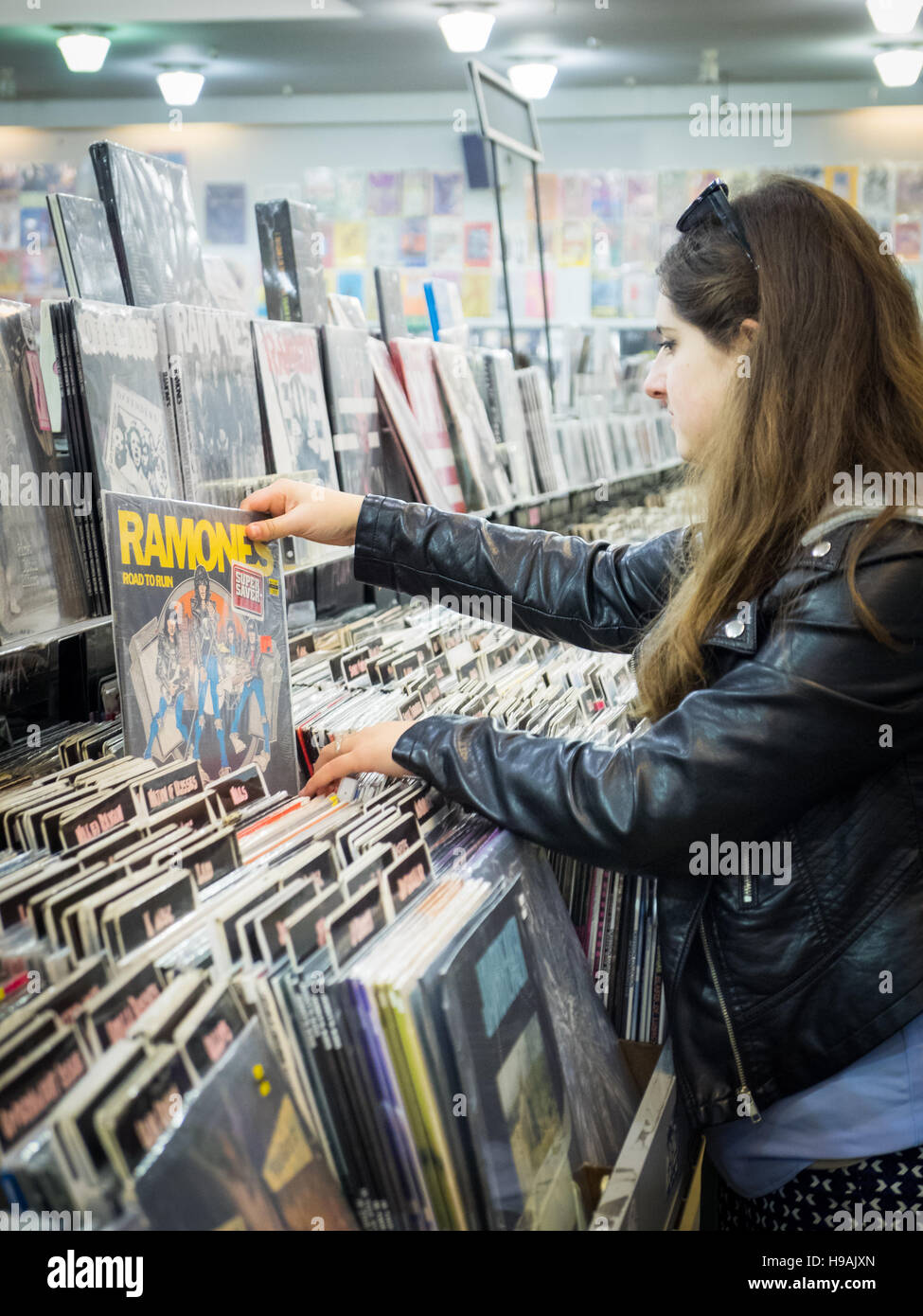 A pretty brunette girl searches for Ramones record albums at Amoeba Music (Amoeba Records) in San Francisco, California. - Stock Image