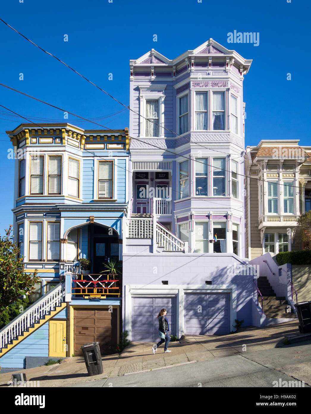 A girl walks up Sanchez Street (note Victorian-Italianate architecture) in the Castro District of San Francisco, - Stock Image