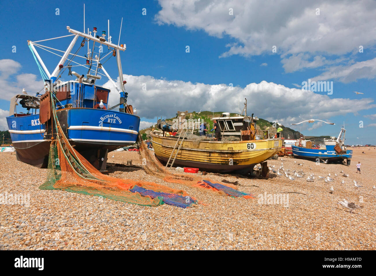 Hastings trawlers with colourful nets drying on the Old Town Stade Fishermen's beach, Rock-a-Nore, Hastings, East Stock Photo