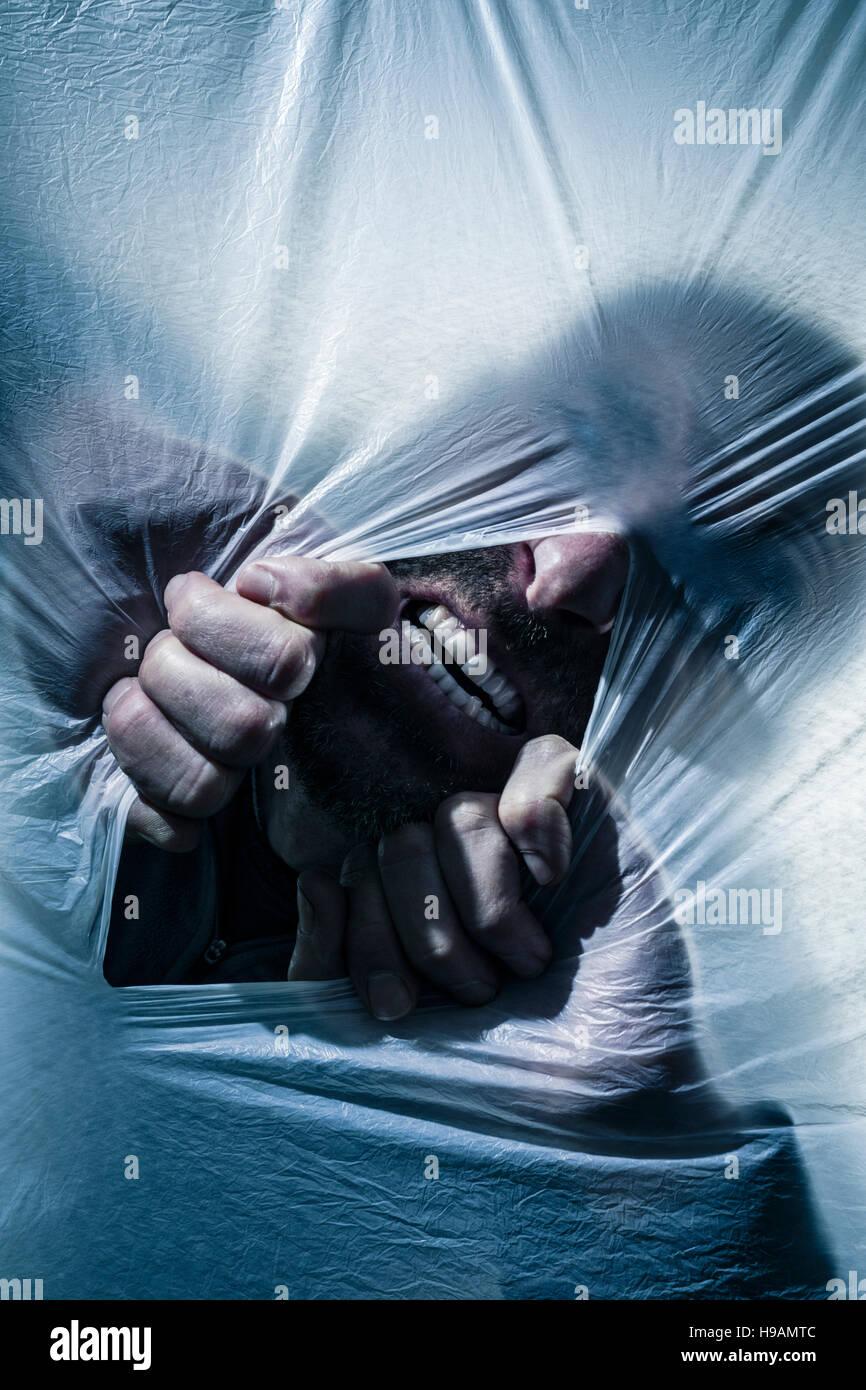 Grimacing man tearing open a polythene screen. - Stock Image