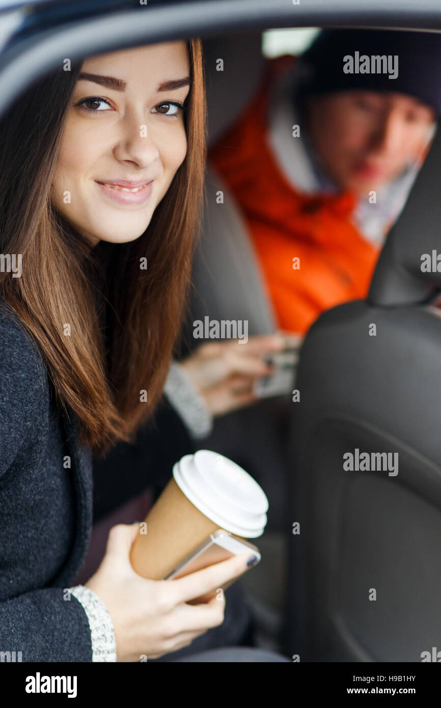 Beautiful brunette sitting in taxi conveys driver money for travel - Stock Image