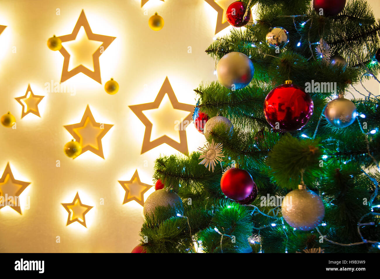 Closeup Of Christmas Tree Background In The Living Room House With Glowing Stars On Wall