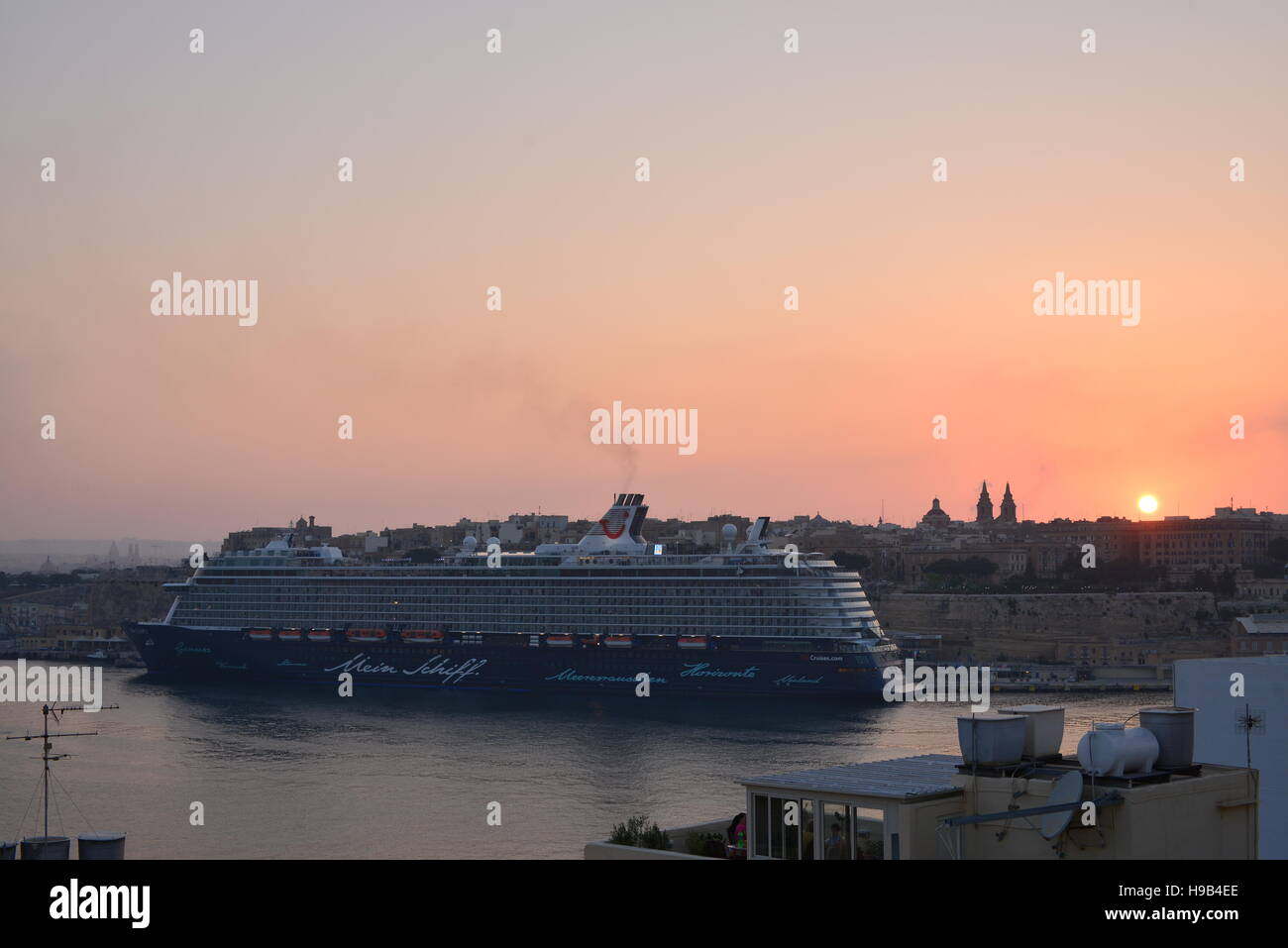 The Mein Schiff 3 cruise ship, operated by TUI, berthed in the Grand Harbour in Malta at sunset - Stock Image