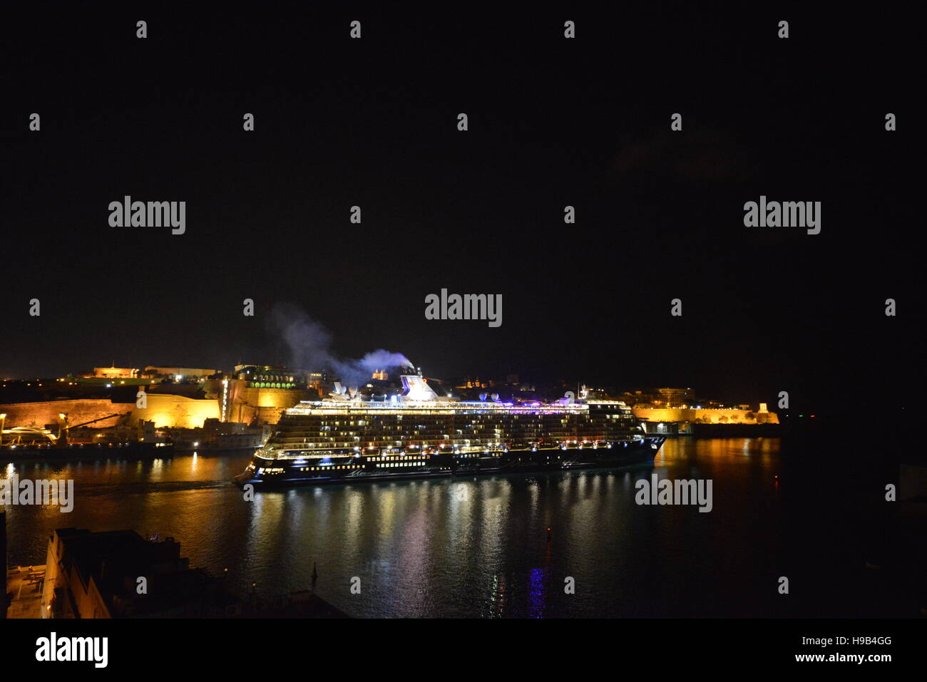 The Mein Schiff 3 cruise ship, operated by TUI, as it was departing the Grand Harbour in Malta at night time - Stock Image