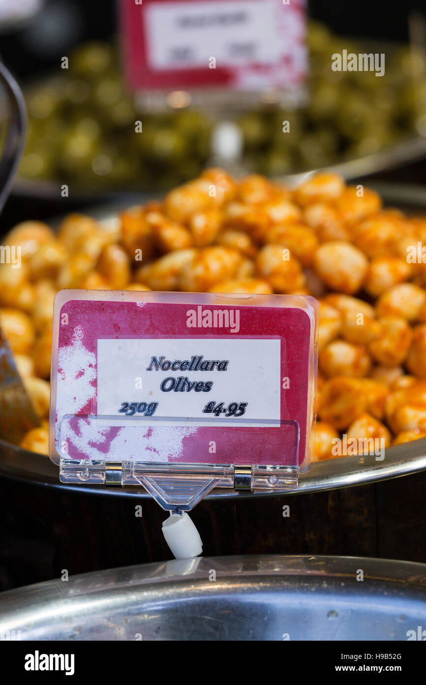 Olives and deli treats in silver bowls with signs and prices, fresh produce at farmers christmas market Stock Photo