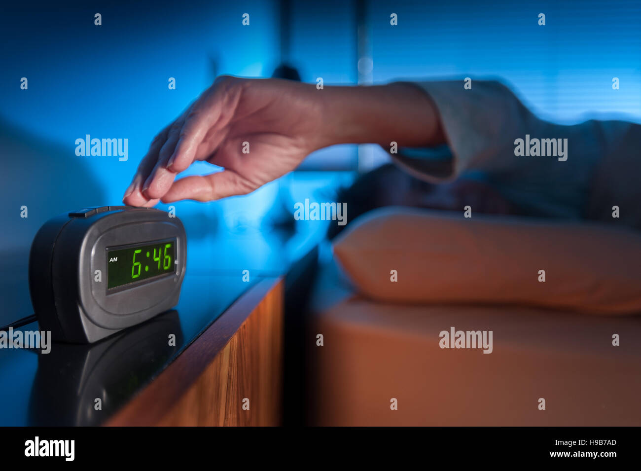 Woman pressing snooze button on early morning digital alarm clock - Stock Image