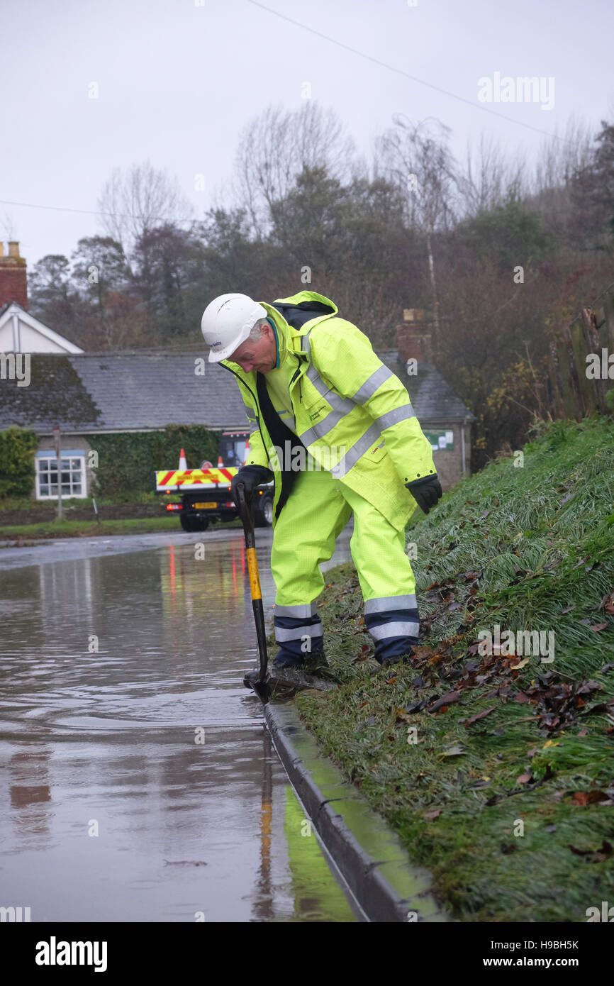 Combe, Herefordshire, UK. 21st November, 2016. A worker from Herefordshire County Council tries to clear blocked - Stock Image