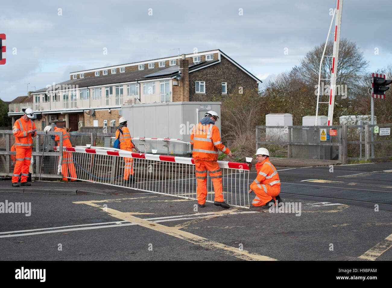 Network Rail engineers repair a railway level crossing