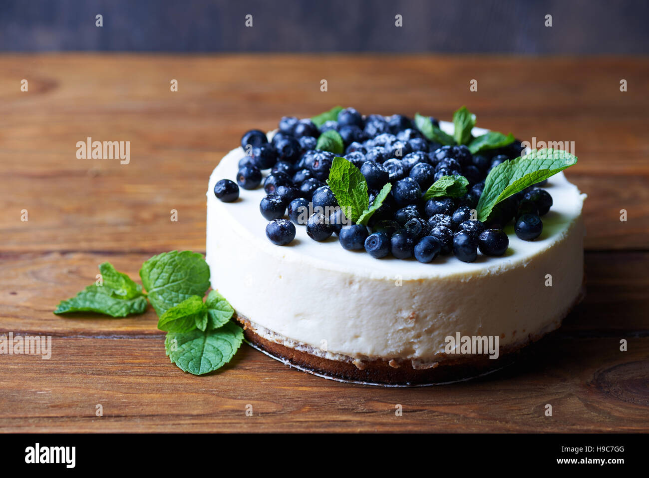 Sweet creamy blueberry cheesecake with fresh blueberries and mint leaves on a wooden background with copy space. - Stock Image