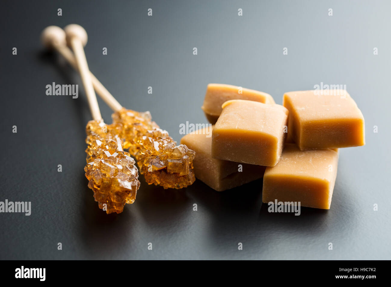 Brown sugar crystals on stick and caramel candies on black background. - Stock Image