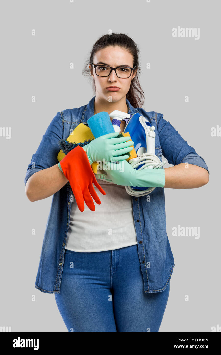 portrait of a tired woman with hands full on cleaning stuff stock
