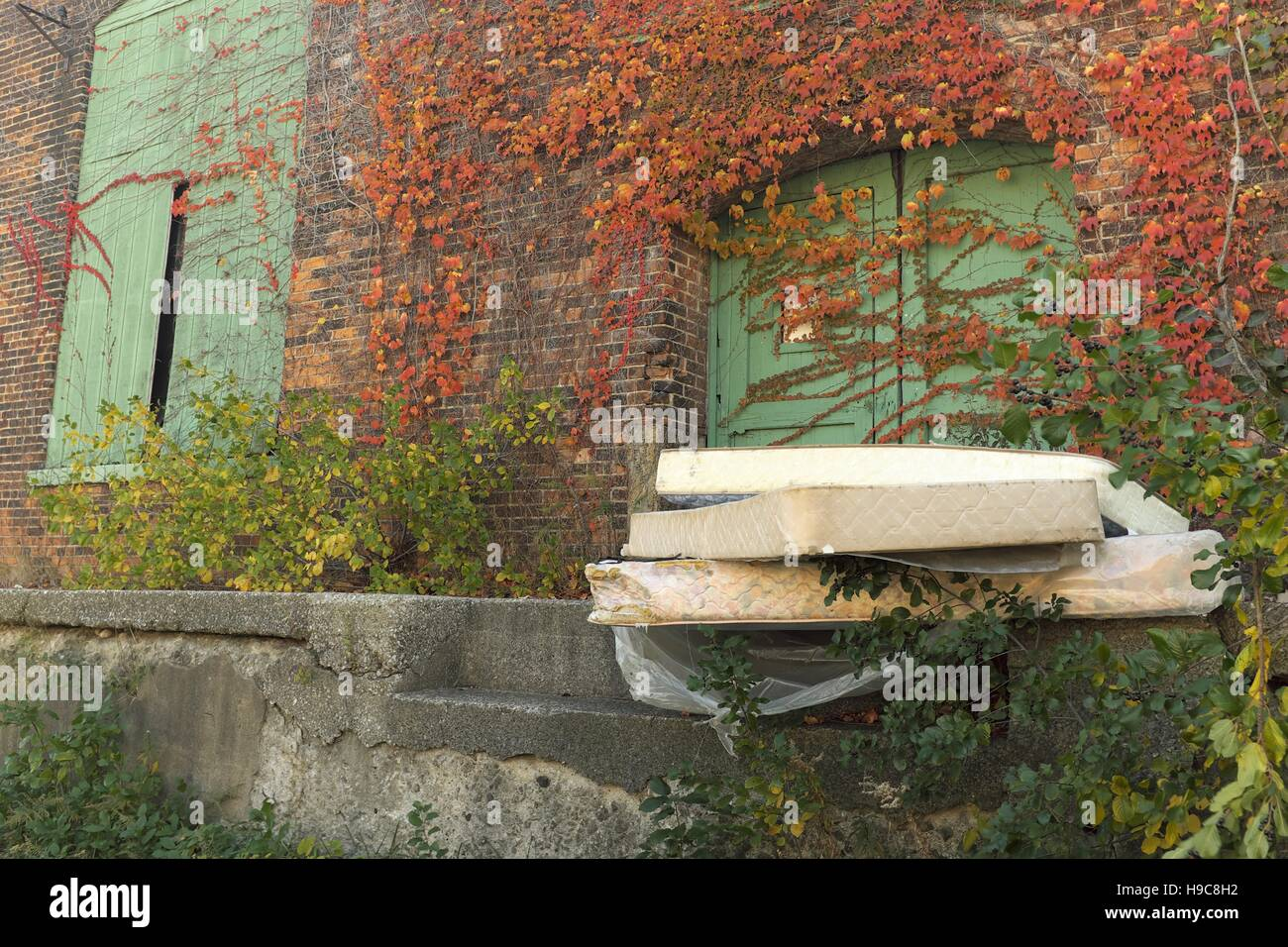 Abandoned mattresses outside a blighted warehouse. - Stock Image