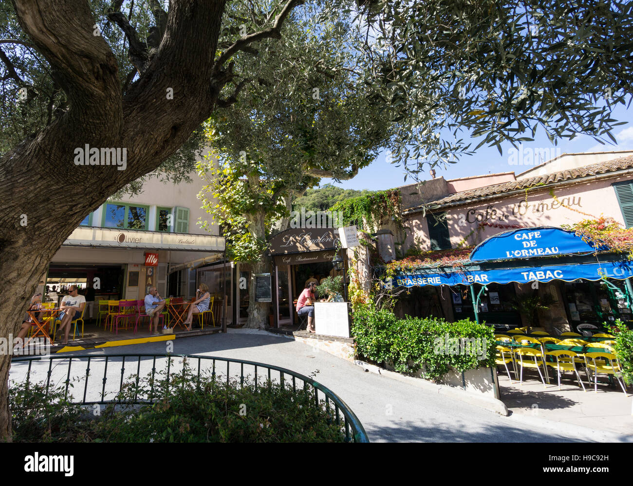 Diners outside cafés in the South of France village of ramatuelle, Var France with large tree and blue sky. - Stock Image