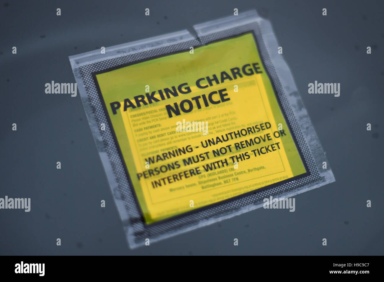 Penalty Charge Notice on windscreen of car. Parking ticket on rainy windscreen - Stock Image